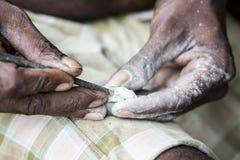 Chiuda su delle mani asiatiche indiane senior dell'intagliatore dello scultore dell'uomo che lavorano alla sua scultura di marmo  Immagine Stock Libera da Diritti