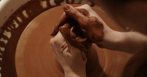 Chiuda su delle mani che funzionano l'argilla sulla ruota del ` s del vasaio, la vista superiore, vista del primo piano video d archivio