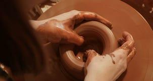 Chiuda su delle mani che funzionano l'argilla sulla ruota del ` s del vasaio, la vista superiore, vista del primo piano stock footage