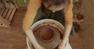 Chiuda su delle mani che funzionano l'argilla sulla ruota del ` s del vasaio, vista del primo piano video d archivio