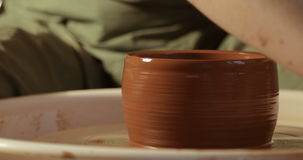 Chiuda su delle mani che funzionano l'argilla sulla ruota del ` s del vasaio, vista del primo piano stock footage