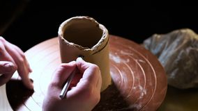 Chiuda su delle mani che funzionano l'argilla sulla ruota del ` s del vasaio Lavoricchii le forme che il prodotto dell'argilla co archivi video