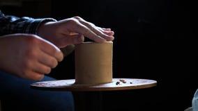Chiuda su delle mani che funzionano l'argilla sulla ruota del ` s del vasaio Lavoricchii le forme che il prodotto dell'argilla co stock footage