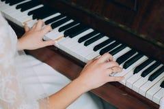 Chiuda su delle mani che giocano il piano Fotografia Stock