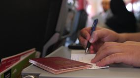 Chiuda su delle mani che maschii il passeggero con il passaporto sta riempiendo nelle carte di arrivo o di migrazione nel volo pi stock footage