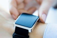 Chiuda su delle mani che mettono l'orologio astuto Fotografie Stock Libere da Diritti