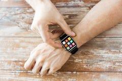 Chiuda su delle mani che mettono l'orologio astuto con le icone Fotografia Stock