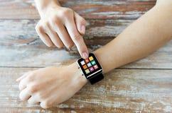 Chiuda su delle mani che mettono l'orologio astuto con le icone Fotografia Stock Libera da Diritti