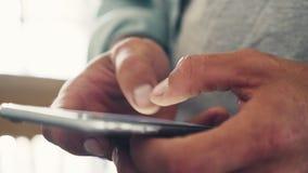 Chiuda su delle mani che scrivono su un telefono in caffè stock footage