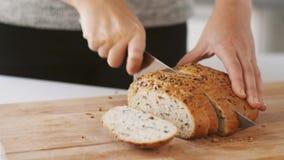 Chiuda su delle mani che tagliano il pane bianco con il coltello stock footage