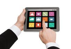 Chiuda su delle mani che tengono il pc della compressa con le icone di app Immagine Stock