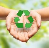 Chiuda su delle mani che tengono il segno di riciclaggio verde Fotografia Stock