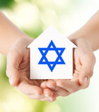 Chiuda su delle mani che tengono la casa con la stella di Davide Fotografia Stock Libera da Diritti