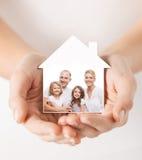 Chiuda su delle mani che tengono la forma della casa con la famiglia Fotografia Stock Libera da Diritti