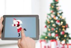 Chiuda su delle mani con il Babbo Natale sul pc della compressa Immagini Stock