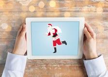 Chiuda su delle mani con il Babbo Natale sul pc della compressa Fotografia Stock Libera da Diritti