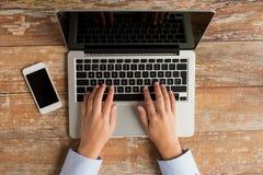 Chiuda su delle mani con il computer portatile e lo smartphone Fotografia Stock