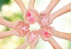 Chiuda su delle mani con il simbolo di consapevolezza del cancro Fotografia Stock