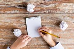 Chiuda su delle mani con il taccuino e la matita Immagini Stock