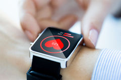 Chiuda su delle mani con l'icona del cuore su smartwatch Immagini Stock