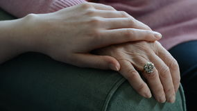 Chiuda su delle mani con la giovane donna che conforta la femmina senior stock footage