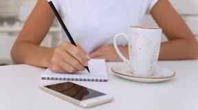 Chiuda su delle mani con la penna che scrive al blocco note con caffè e lo smartphone sulla tavola immagine stock libera da diritti