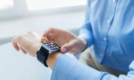 Chiuda su delle mani con le icone del menu sull'orologio astuto Immagine Stock