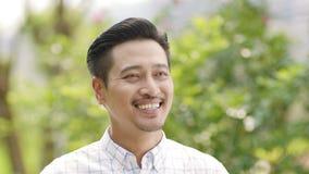 Chiuda su delle mani d'ondeggiamento dell'uomo asiatico, sorridendo arrivederci stock footage