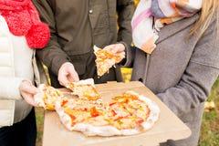 Chiuda su delle mani degli amici che mangiano la pizza all'aperto Immagine Stock