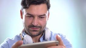 Chiuda su delle mani degli uomini che tengono il contatto del telefono cellulare del gioco del gioco archivi video