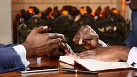 Chiuda su delle mani degli uomini nel corso della riunione d'affari Gesturing attivo, scrivendo le note Afroamericani in vestiti  video d archivio