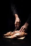 Chiuda su delle mani dei cuochi unici che tagliano le baguette a pezzi su fondo nero Immagini Stock