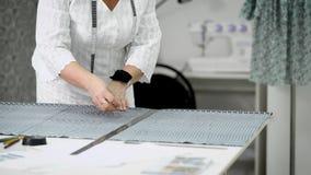 Chiuda su delle mani dei sarti femminili che stanno alle linee del disegno della tavola sul panno con gesso Sarto da donna profes stock footage