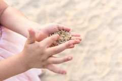 Chiuda su delle mani del bambino che giocano con la sabbia immagine stock libera da diritti