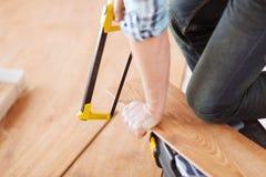 Chiuda su delle mani del maschio che tagliano l'asse del pavimento del parquet Fotografie Stock Libere da Diritti