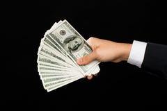 Chiuda su delle mani del maschio che tengono il denaro contante del dollaro Fotografia Stock