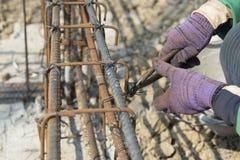 Chiuda su delle mani del muratore che funzionano con le tenaglie Immagine Stock