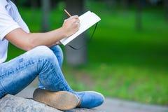Chiuda su delle mani del ragazzo che studiano per l'esame dell'istituto universitario Immagini Stock