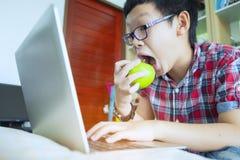 Chiuda su delle mani del ragazzo con la mela verde e di esame del computer portatile Fotografia Stock Libera da Diritti