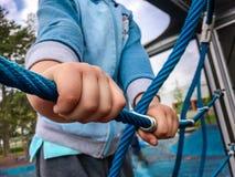 Chiuda su delle mani del ragazzo tiene la corda sulla rete rampicante della corda fotografia stock
