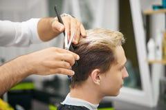 Chiuda su delle mani del ` s del barbiere che fanno il nuovo taglio di capelli per il giovane cliente immagini stock libere da diritti