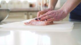 Chiuda su delle mani del ` s della donna che tagliano la carne in 4K archivi video