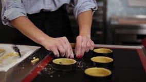 Chiuda su delle mani del ` s della donna con il manicure rosso che modella e che prepara la pasta del biscotto per cuocere facend stock footage