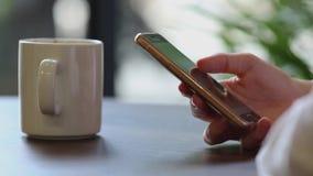 Chiuda su delle mani del ` s della donna facendo uso del telefono cellulare alla pausa caffè video d archivio