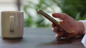 Chiuda su delle mani del ` s della donna facendo uso del telefono cellulare alla pausa caffè archivi video