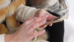 Chiuda su delle mani del ` s della ragazza facendo uso del telefono cellulare all'aperto nell'inverno archivi video