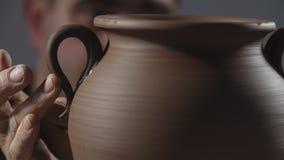 Chiuda su delle mani delicatamente creano la brocca da argilla Il vasaio crea il prodotto stock footage