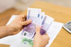 Chiuda su delle mani dell'uomo che contano i soldi a casa Fotografia Stock