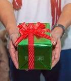 Chiuda su delle mani dell'uomo che giudicano un contenitore di regalo avvolto con il nastro rosso Fotografia Stock