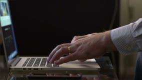 Chiuda su delle mani dell'uomo che scrivono su una tastiera del computer portatile stock footage